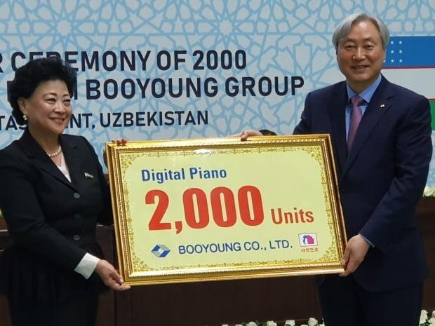 신현석 부영그룹 고문(오른쪽)이 아그리피나 신 우즈베키스탄 유아교육부 장관과 함께 디지털피아노 2000대 기증판을 들어보이고 있다.