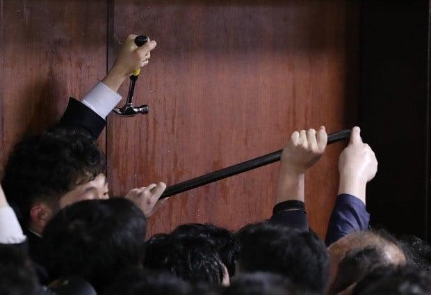 더불어민주당 의원과 보좌관들이 26일 새벽 여야4당의 수사권조정법안을 제출하기 위해 자유한국당 당직자들이 점거하는 국회 의안과에 '도구'를 사용해 진입 시도하고 있다. (사진=연합뉴스)