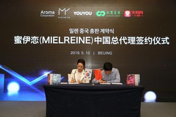 임미숙 아로마무역 대표(왼쪽)와 라이쉐이량 따샹그룹 부총재가 지난 10일 중국 베이징에서 열린 밀렌 중국 총판 계약식에서 서명하고 있다. < 아로마무역 제공 >