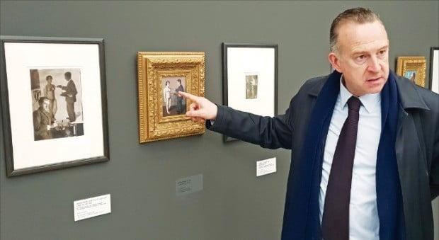 자비에 카노네 샤를루아미술관장이 뮤지엄그라운드에 전시된 르네 마그리트의 사진을 설명하고 있다.