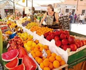 베네치아 오래된 골목길의 과일상점에서 과일을 고르는 여인