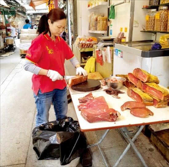 홍콩 전통시장에서 옛날식으로 고기를 잘라 파는 상인.