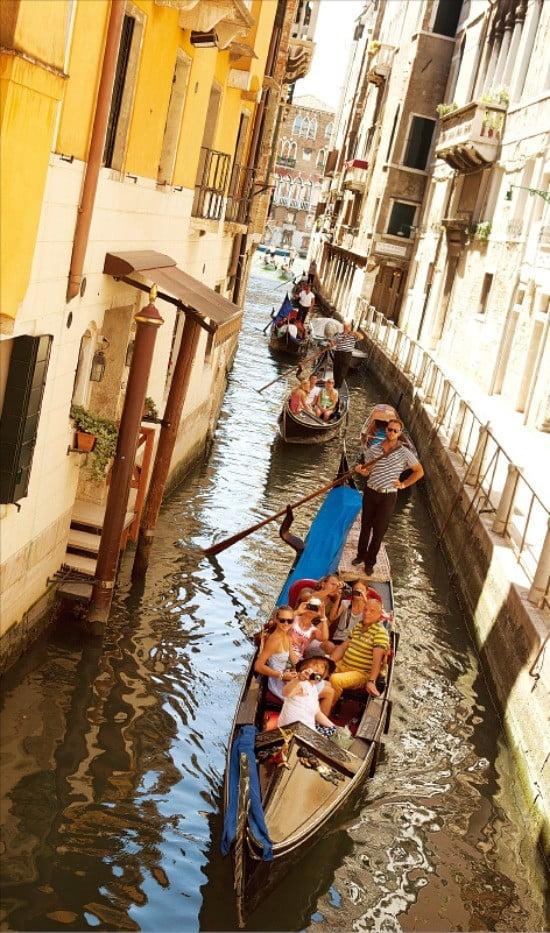 곤돌라를 타고 건물 사이 좁은 수로를 지나는 관광객들