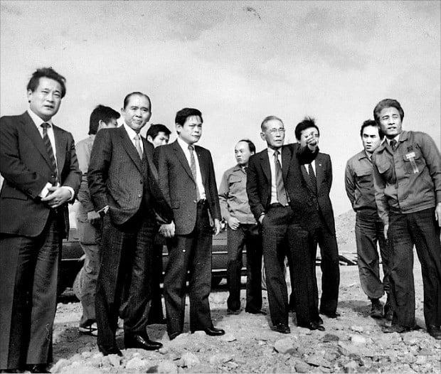 1983년 경기 용인시 기흥 반도체공장 건설 현장을 둘러보는 이병철 삼성그룹 창업주(앞줄 왼쪽 네 번째)와 이건희 삼성 회장(세 번째).  /한경DB