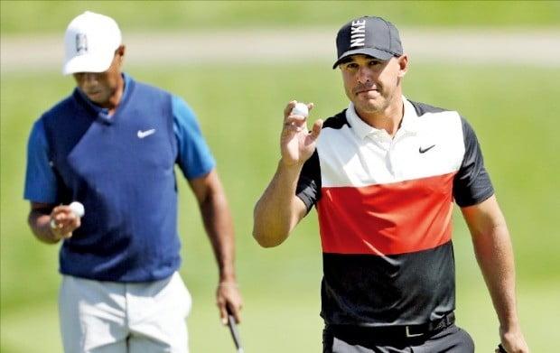 브룩스 켑카가 17일(한국시간) 열린 PGA챔피언십 1라운드 18번홀에서 버디를 잡아낸 뒤 공을 들어보이며 갤러리들의 박수에 화답하고 있다. 타이거 우즈와 한 조로 경기한 켑카(7언더파)는 우즈(2오버파)를 9타 차로 밀어내고 단독 선두에 올라섰다.  /AFP연합뉴스