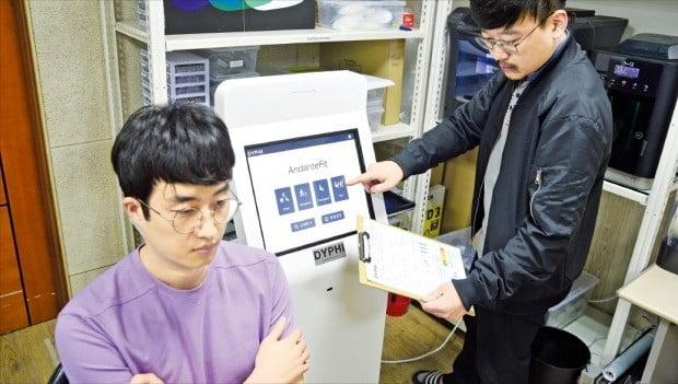 KAIST 실험실 스타트업 디파이의 노현철 대표(오른쪽)가 28일 대전 본사 연구실에서 조영근 엔지니어(왼쪽)와 함께 근감소증 측정기기 '안단테-핏'을 테스트하고 있다.  /디파이  제공