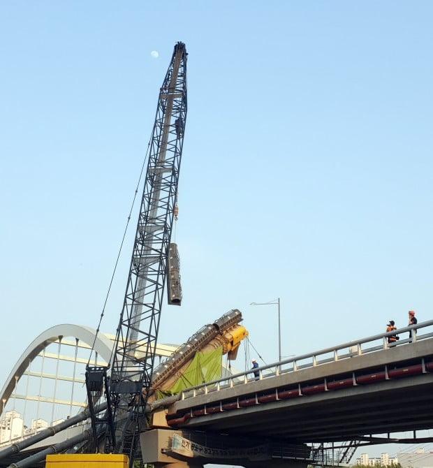 15일 오후 서울 구로구 구로동 안양교 인근 공사 현장에서 굴착 장비가 다리 위로 넘어져 양방향 차로의 통행이 막혔다. 사진은 크레인이 다리로 넘어진 건설장비를 치우는 모습/사진=구로소방서