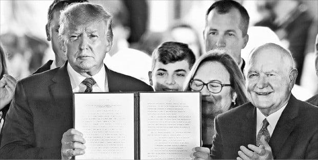 도널드 트럼프 미국 대통령(왼쪽)이 11일(현지시간) 아이오와주 카운슬 블러프즈에서 미국산 유전자변형작물(GMO)의 유통과 수출을 촉진하기 위해 서명한 행정명령서를 들어 보이고 있다.  /AFP연합뉴스