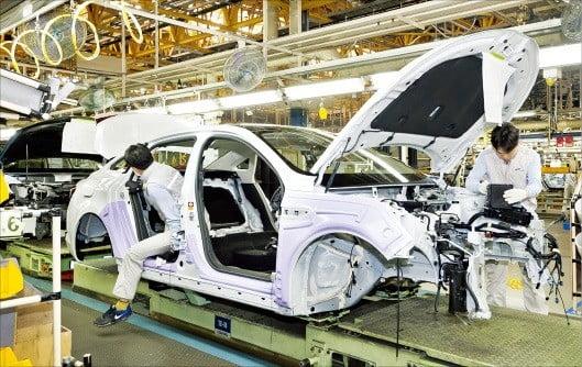 부산 녹산공단에 있는 르노삼성자동차 부산공장 직원들이 자동차 생산라인에서 차량을 점검하고 있다.  /르노삼성차 제공