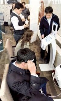 NH투자증권 임직원들이 옴니씨앤에스의 두뇌건강 측정기기를 체험하고 있다.  /옴니씨앤에스 제공