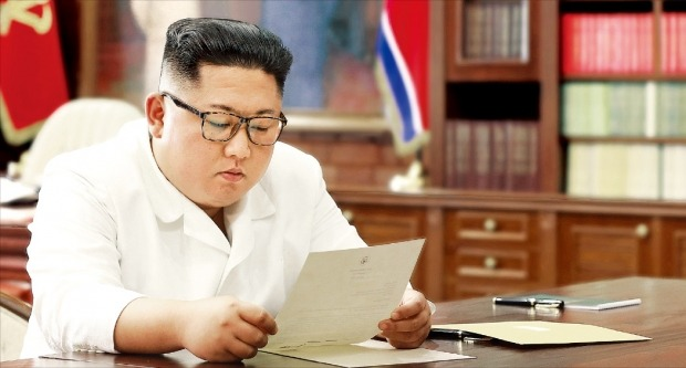 """< 트럼프 친서 읽는 김정은…굵은 밑줄 무슨 내용? > 김정은 북한 국무위원장이 집무실에서 도널드 트럼프 미국 대통령이 보낸 친서를 읽고 있는 모습을 조선중앙통신이 23일 홈페이지에 공개했다. 친서 뒷면에 굵은 밑줄이 두 줄 그어진 모습이 비친다(작은 사진). 김정은이 """"흥미로운 내용""""이라고 언급한 부분일 것이라는 분석이 나온다. 친서 상단에는 미국 대통령 문장(紋章)이, 하단에는 트럼프 대통령의 서명이 보인다. /조선중앙통신/연합뉴스"""