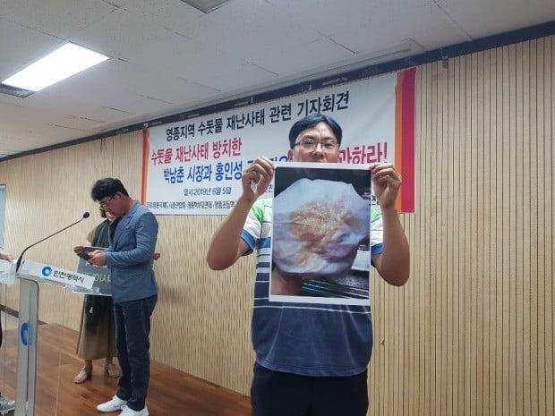 인천 영종국제도시 주민이 5일 인천시청에서 열린 기자회견에서 붉은 수돗물이 나오는 증거 사진을 기자들에게 보여주고 있다. 강준완 기자