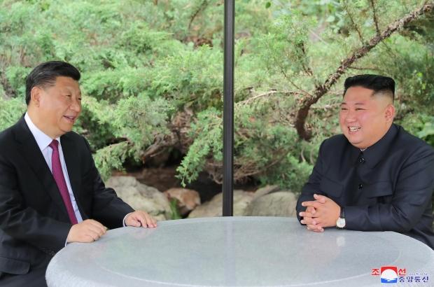 산책 중 자리에 앉아 대화하는 시진핑 중국 국가주석과 김정은 북한 국무위원장. 연합뉴스