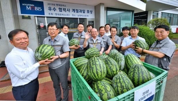 경기도 안산시 남양넥스모㈜ 대표와 직원들이 현대모비스가 전달한 수박을 들어보이며 활짝 웃고 있다.