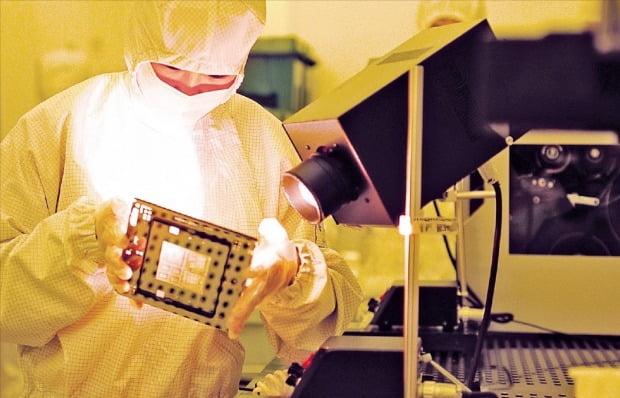 경기 화성시에 있는 삼성전자 반도체공장 클린룸에서 직원이 웨이퍼 원판 위 회로를 만드는 데 쓰이는 기판인 포토마스크를 점검하고 있다.  /삼성전자 제공
