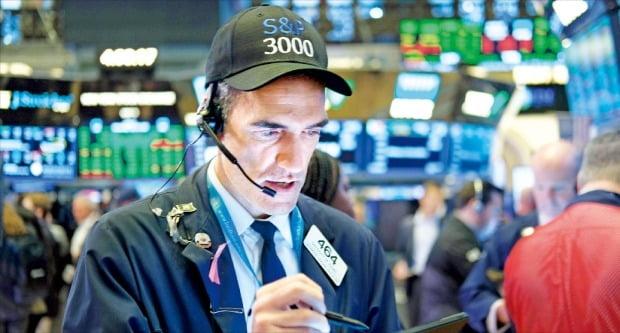 < S&P500 장중 첫 3000 돌파 > 제롬 파월 미국 중앙은행(Fed) 의장이 10일(현지시간) 금리 인하를 시사하자 미국 3대 주가지수가 일제히 사상 최고치를 기록했다. 'S&P500지수 3000 돌파'를 기원하는 모자를 쓴 중개인이 이날 뉴욕증권거래소(NYSE) 객장에서 주문을 처리하고 있다.   /AFP연합뉴스