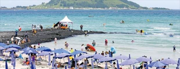 바다 건너 비양도가 보이는 제주시 한림읍 협재해수욕장에서 관광객들이 물놀이를 하며 즐거운 한때를 보내고 있다.한경DB