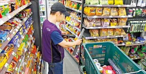 내년도 시간당 최저임금이 올해보다 240원(2.9%) 오른 8590원으로 결정됐다. 12일 서울 시내 한 편의점에서 점주가 상품을 진열하고 있다.  /강은구 기자 egkang@hankyung.com