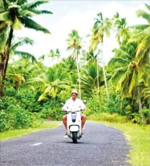 스쿠터를 타고 라로통가섬 여행을 즐기는 여행객