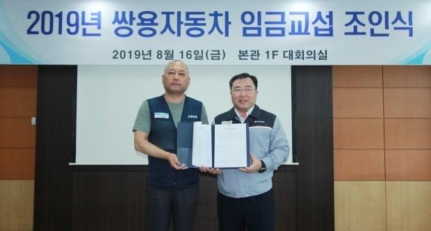 예병태 쌍용자동차 대표이사(오른쪽)와 정일권 노동조합위원장이 임금협상 합의서에 서명한 뒤 기념촬영을 하고 있다.