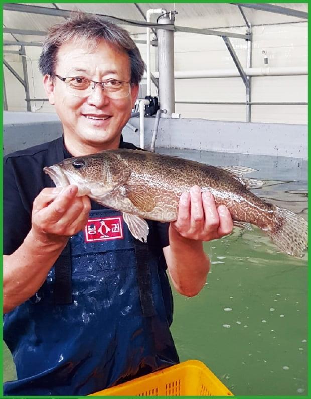 김진규 한국쏘가리연구소 대표가 직접 키운 양식 쏘가리를 들고 있다.