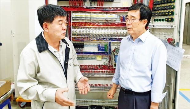 서호전기의 이상호 회장(오른쪽)과 김승남 사장이 안양 공장 내 항만 자동화 크레인 컨트롤러 앞에서 영상인식 기술 개발과 관련해 의견을 나누고 있다.