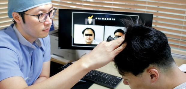 이승용 모건피부과의원 원장이 탈모 환자의 두피 상태를 살펴보고 있다. 모건피부과의원 제공