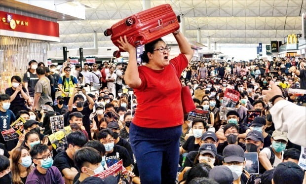 < 또 공항 점거…'폭풍전야' 홍콩 > '범죄인 인도법 개정안'(일명 송환법)에 반대하는 홍콩 시민들이 전날에 이어 13일에도 홍콩국제공항에 모여 시위를 벌였다. 시위대가 공항을 점거해 홍콩국제공항 측은 이날 오후 4시30분 이후 출발하는 모든 항공편의 운항을 중단했다. 홍콩국제공항에선 전날 230여 편에 이어 이날도 300편 이상의 비행기가 결항했다. 한 여행객(가운데)이 시위대를 뚫고 출국장에 들어가려 애쓰고 있다.   /AFP연합뉴스