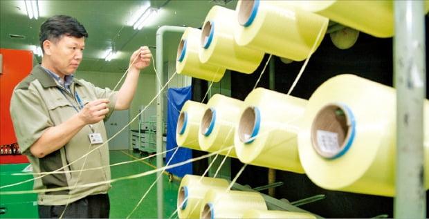 경북 구미에 있는 코오롱인더스트리 공장에서 한 직원이 아라미드 섬유인 헤라크론의 품질을 점검하고 있다.  /코오롱 제공