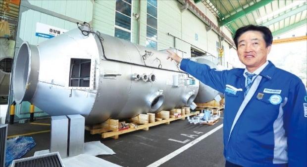 이수태 파나시아 회장이 부산 강서구에 있는 공장 앞에서 스크러버를 가리키고 있다.   /김태현 기자