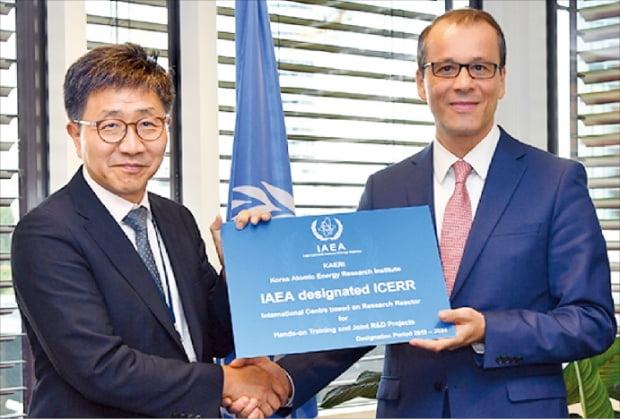 박원석 한국원자력연구원장(왼쪽)이 코넬 페루타 IAEA 사무총장대행으로부터 '하나로 국제연구용원자로센터' 현판을 전달받고 있다.  한국원자력연구원 제공