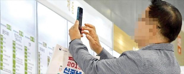 지난 17일 서울 양재동 aT센터에서 열린 '2019년 신중년 인생3모작 박람회'에서 한 구직자가 채용정보를 자신의 스마트폰으로 찍고 있다.   김영우 한국경제신문 기자 youngwoo@hankyung.com