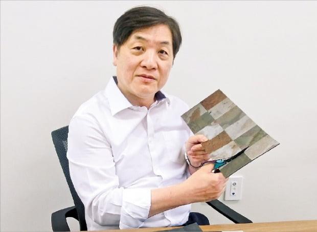 김형진 유니디자인 사장이 '리얼스톤 타일 스티커' 사용법을 설명하고 있다.  /김진수 기자