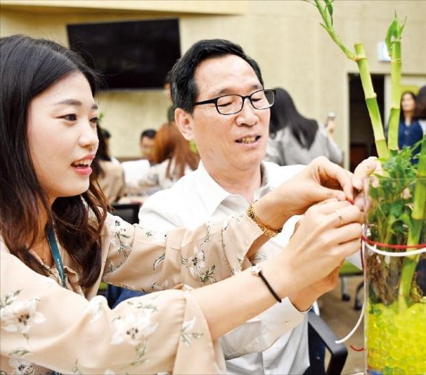 이병호 한국농수산식품유통공사(aT) 사장이 지난 9월 26일 광주·전남지역 어르신들에게 전달할 테라리움(공기정화식물 화분)을 만들고 있다.  aT센터 제공