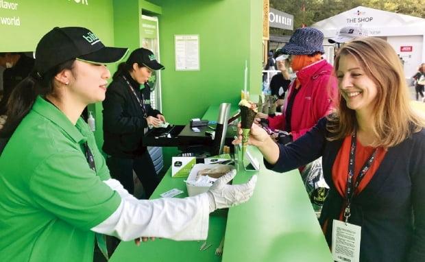 미국프로골프(PGA)투어 대회인 '더 CJ컵 나인브릿지' 경기장에 마련된 비비고 부스에서 한 외국인이 아이스크림콘 모양 비빔밥인 '비비콘'을 받아들고 있다.  CJ 제공