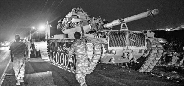 8일(현지시간) 시리아와 접하고 있는 터키 남동부 샨리우르파주 국경 지역에서 터키군 탱크가 트럭에서 내려오고 있다.  AFP연합뉴스