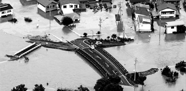 19호 태풍 '하기비스'가 강타한 일본 나가노시에서 제방이 붕괴돼 마을과 다리가 물에 잠겼다.   /AP연합뉴스