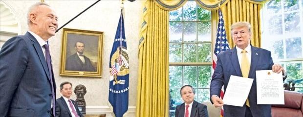 < 활짝 웃는 중국 무역협상단 대표 > 도널드 트럼프 미국 대통령(오른쪽)이 지난 11일 미국 워싱턴DC 백악관 집무실에서 중국 무역협상단 대표인 류허 부총리(왼쪽)로부터 전달받은 시진핑 국가주석의 친서를 취재진에게 보여주고 있다.  /EPA연합뉴스