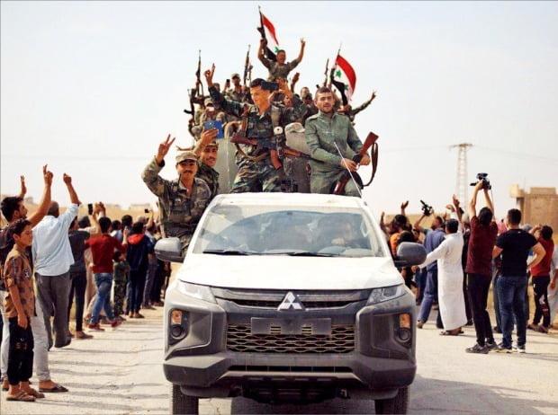 < 시리아군 환영하는 쿠르드족 > 쿠르드족 주민들이 14일 시리아 북부 아인 이사에서 시리아 정부군의 진입을 환영하고 있다. 쿠르드족은 터키의 공습을 막기 위해 그간 대립했던 시리아 정부군에 자치지역 진입을 허용하기로 했다. 전날 미군은 아인 이사 기지에서 전원 철수했다.  /AP연합뉴스