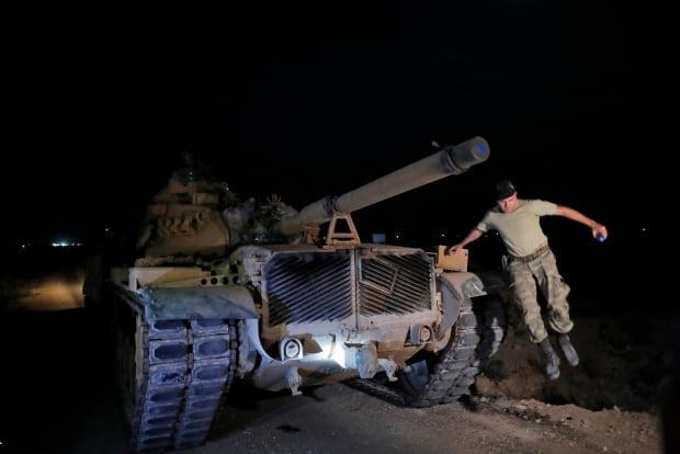 터키군 탱크가 8일(현지시간) 시리아와 접하고 있는 남동부 샨르우르파주 국경지역의 새 진지에 도착하자 한 장교가 밖으로 뛰어내리고 있다. /사진=연합뉴스