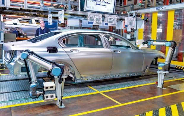 독일 딩골핑에 있는 BMW 공장에서 직원과 로봇이 함께 작업하고 있다.  BMW  제공