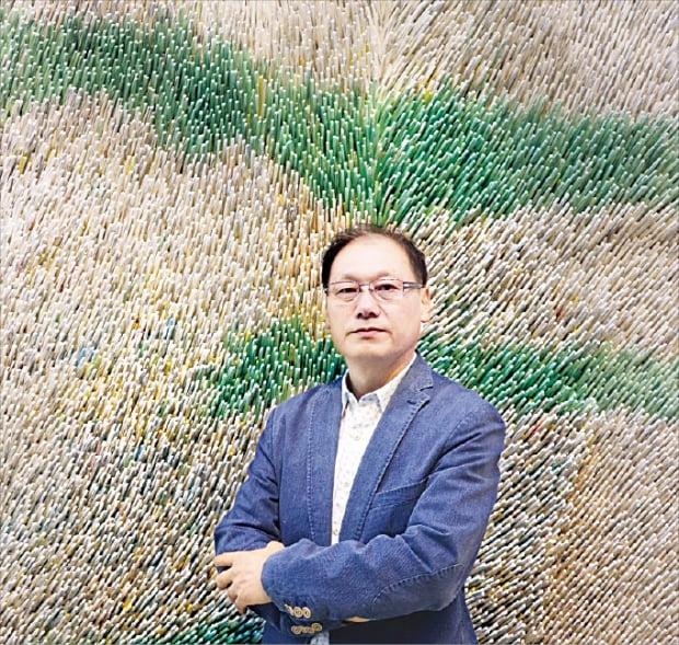 한지 조형미술가 서정민 씨가 경기 파주 갤러리 박영의 개인전에 출품한 작품을 설명하고 있다.