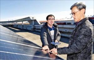 건물 옥상에 설치된 태양광 패널을 살펴보고 있는 조경목 SK에너지 사장(오른쪽).  SK에너지 제공