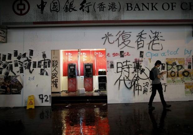 홍콩 시위대의 공격으로 파손된 중국은행 한 지점의 현금자동입출금기(ATM)와 각종 구호가 적힌 벽./사진=연합뉴스