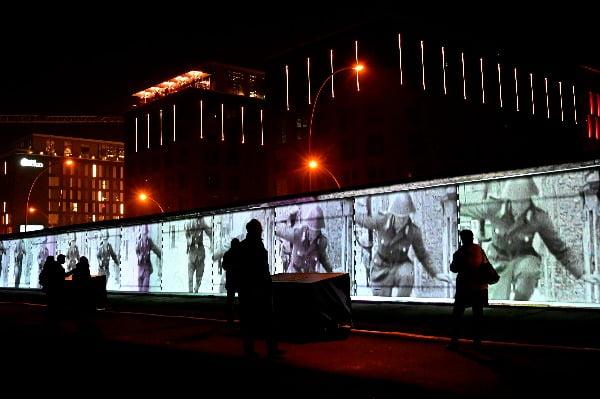베를린에서 관람객들이 1.3km의 베를린 장벽 일부인 '이스트사이드 갤러리' 위로 투사되는 3D 영상을 보고 있다. 베를린 장벽 붕괴 30주년을 기념해 베를린에서는 3만 명의 소망과 기억을 담은 리본 3만 개로 만들어진 그물이 4일부터 오는 10일까지 전시된다/사진제공=연합뉴스