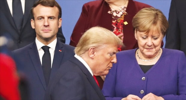 도널드 트럼프 미국 대통령(앞쪽)이 4일 영국 왓퍼드 그루브호텔에서 열린 북대서양조약기구(NATO) 정상회의 기념촬영 자리를 잡기 위해 에마뉘엘 마크롱 프랑스 대통령(뒷줄 왼쪽)과 앙겔라 메르켈 독일 총리 앞을 걸어가고 있다.  AP연합뉴스