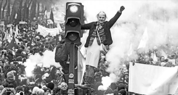 < 파리 점령한 시위대 > 프랑스에서 근로자 150만여 명이 정부의 연금개혁에 반대하는 시위를 벌였다. 프랑스 파리에서 5일(현지시간) 한 시민이 신호등에 올라가 파업 지지를 촉구하고 있다.  AP연합뉴스