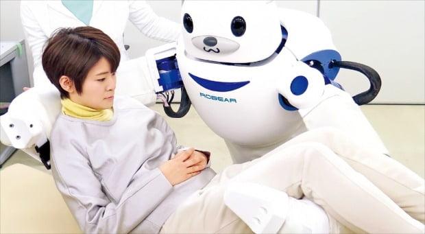 실버산업은 '노인 대국' 일본에서 가장 빠르게 성장하는 산업이다. 2025년에는 노인시장 규모가 1076조원에 달할 것이란 전망이 나올 정도다. 사진은 2015년 일본 이화학연구소가 개발한 돌봄 로봇 '로베아'가 여성을 침대로 옮기는 장면.   /연합뉴스