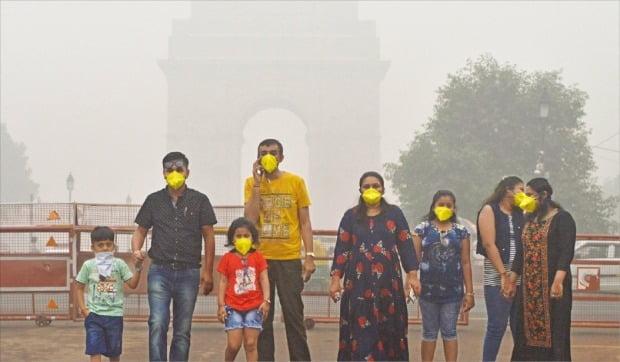 미세먼지에 가려진 인디아게이트 세계에서 대기 오염이 가장 심한 도시로 꼽히는 인도 뉴델리의 상징물인 인디아게이트 앞에서 지난달 3일 관광객들이 마스크를 쓰고 기념사진을 찍고 있다. 미세먼지가 심한 탓에 100m도 떨어지지 않은 인디아게이트가 겨우 형체만 보인다.  /신화연합뉴스