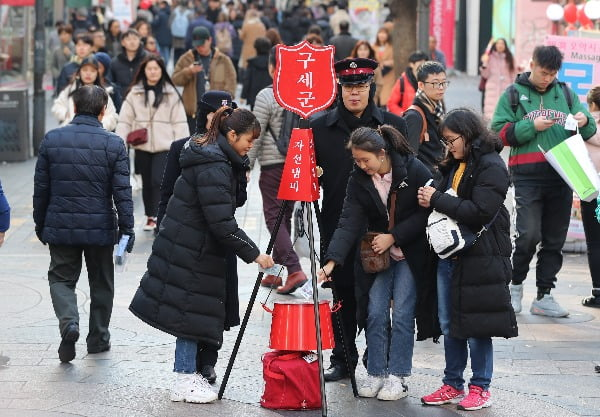 11일 서울 중구 명동에서 학생들이 성금을 자선냄비에 넣고 있다/사진=연합뉴스